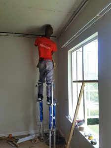 Man On Stilts Doing A Residential Ceiling Installation